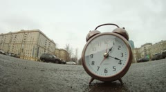 Clocks stands on roadside of road in front of moving cars Stock Footage
