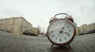 Stock Video Footage of Clocks stands on roadside of road in front of moving cars