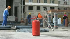 Extinguisher stands in front of  workers which work with fire on housing estate Stock Footage