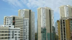 Clouds in blue sky float above considerable quantity of new buildings - stock footage