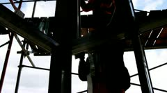 Silhouettes of workers are visible behind glass on scaffold Stock Footage
