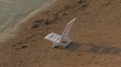 135 WHITE PLASTIC CHAIR ON THE BEACH Stock Footage