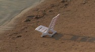 Stock Video Footage of 135 WHITE PLASTIC CHAIR ON THE BEACH