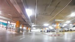 Car goes between other cars in underground parking Stock Footage
