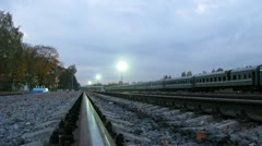 Passenger train stands at railway station before empty rails Stock Footage