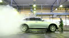 Steam clubs cover car which is washed on car wash with workers Stock Footage
