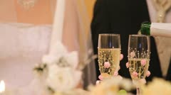 In two glasses champagne on wedding  is poured Stock Footage