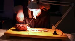 Hands of cook knife big piece of smoking meat by light of lamp Stock Footage