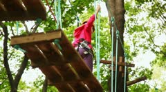 Girl goes on boards suspended in wood, strong keeping for ropes Stock Footage