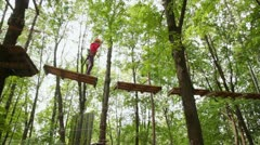 Girl walks on suspended by cables on trees in wood to boards Stock Footage