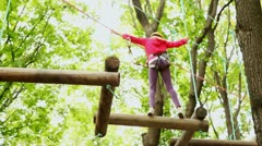 Girl crosses on linked logs and suspended on height in wood Stock Footage