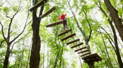 Girl fixed on insurance, jumps on suspended by ropes on trees to logs Stock Footage