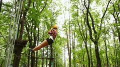 Girl moves down downwards suspended on cable in wood between trees Stock Footage