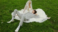 Groom lies in lap at bride and on its wedding dress and together they have rest Stock Footage