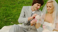 Newly-married couple sitting on meadow are fastened to handcuffs Stock Footage