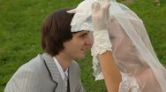 Newly-married couple sits on grass together and kisses under veil of bride Stock Footage