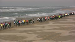 Crowds take part in a half marathon run at the beach in the Netherlands Stock Footage