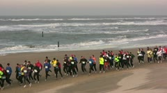 Recreational marathon runners on the beach, waves at sea, sports outdoors Stock Footage