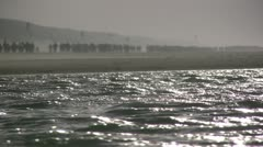 Marathon runners in the distance behind sea water Stock Footage