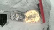 Cleaning snow off headlight Stock Footage