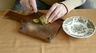 Old woman hands cut up kiwi Stock Footage