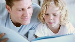 Child reading a book aloud with his father Stock Footage