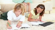 Siblings coloring together Stock Footage