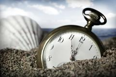 old pocket watch buried in sand - stock photo