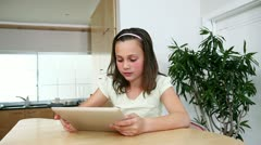 Girl with a tablet computer in the kitchen Stock Footage