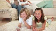 Siblings lying on the floor and watching tv with parents behind them Stock Footage