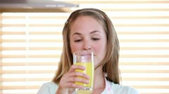 Smiling woman drinking orange juice - stock footage