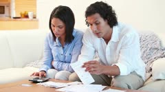 Couple on the sofa calculating their expenses Stock Footage
