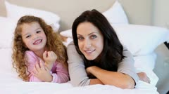 Mother and daughter lying on the bed Stock Footage