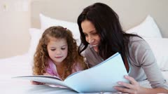 Woman reading a story for her daughter Stock Footage