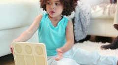 Girl playing with toy blocks while her parents sit on the sofa Stock Footage