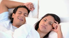 Annoyed woman lying next to her snoring boyfriend Stock Footage