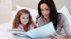 Mother reading a book with her daughter Stock Footage
