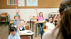 Pupils raising their fingers in front of the teacher - stock footage