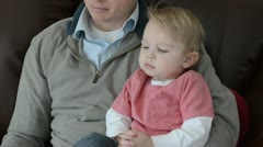 Toddler boy and baby sitting on dads lap 8968 Stock Footage
