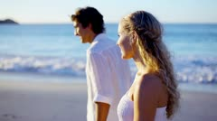 Couple on the beach walking towards the sunset while holding hands Stock Footage