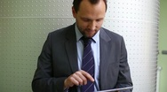 Businessman with tablet computer standing by the wall, steadicam shot Stock Footage