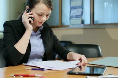 Businesswoman with documents talking on cellphone in office, steadicam shot - stock footage