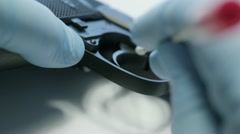 Police CSI swabbing gun for suspect DNA traces Stock Footage