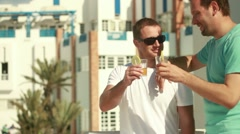 Gay couple enjoying drinks in exotic hotel, outdoors, steadicam shot HD Stock Footage