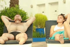 Couple relaxing on sunbeds, outdoors, steadicam shot NTSC Stock Footage