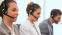 Call centre agents talking with headsets - stock footage