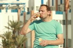 Sad man drinking exotic cocktail, outdoors, steadicam shot NTSC Stock Footage