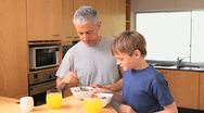 Father and son eating their breakfast Stock Footage