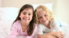Smiling siblings lying on a bed Stock Footage