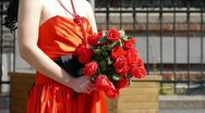 Bride wearing a red wedding dress,carrying a bouquet of rose flowers. Stock Footage